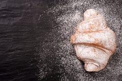 一个新月形面包洒与在黑石背景的搽粉的糖与您的文本的拷贝空间 顶视图 免版税库存照片