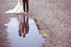 一个新郎和新娘的反射在水中 免版税库存图片