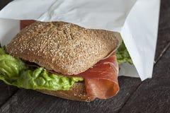 一个新鲜的德国小圆面包用火腿和沙拉 免版税库存图片