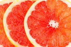 一个新鲜的成熟水多和开胃葡萄柚和它的零件特写镜头,在白色背景 免版税库存照片