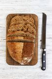 一个新鲜的面包和一把面包刀在一张土气老白色桌上 面包剪切牌照片式 免版税库存图片