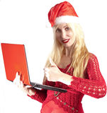 一个新年的帽子的年轻美丽的妇女有红色膝上型计算机的 库存图片