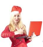 一个新年的帽子的年轻美丽的妇女有红色膝上型计算机的 图库摄影