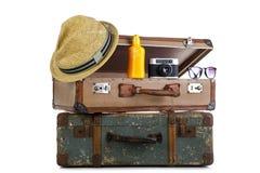 一个旅客的减速火箭的手提箱有帽子的,照相机,晒黑奶油和 库存照片