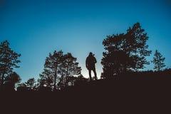 一个旅客的剪影在一个森林中间的有一个背包和一把吉他的反对天空蔚蓝背景 库存照片