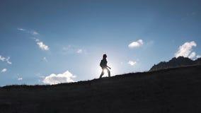 一个旅客的剪影在山和天空背景中  旅游女孩沿小山的上面走 股票视频