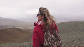 一个旅客的画象山的在倾吐的雨下 单独旅游女孩有在高地的一个背包的 股票录像
