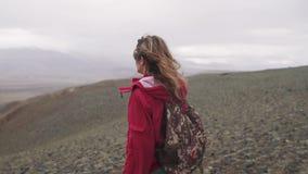 一个旅客的画象山的在倾吐的雨下 单独旅游女孩有在高地的一个背包的 股票视频