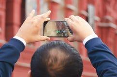 一个旅游人在红场拍在电话的照片在莫斯科 免版税库存图片