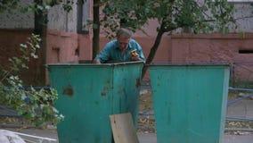 一个无家可归的人在一个绿色垃圾箱开掘在房子,寻找在垃圾箱的叫化子老人附近食物 股票视频