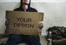 一个无家可归的人拿着设计空间板 图库摄影