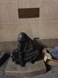 一个无家可归的叫化子的雕象 库存照片