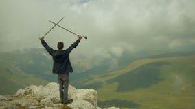 一个无忧无虑和自由的男孩举了他的手并且看天空 在上面攀登的年轻背包徒步旅行者 股票录像