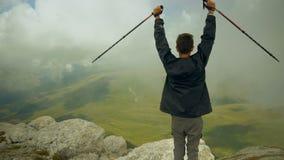 一个无忧无虑和自由的男孩举了他的手并且看天空 在上面攀登的年轻背包徒步旅行者 股票视频