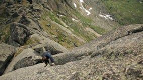 一个无私的人在峭壁的上面上升,不用绳索 影视素材