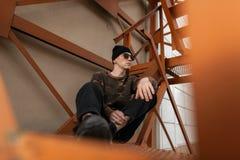 一个时兴的帽子的美国年轻行家人在葡萄酒军用衬衣的黑太阳镜在的牛仔裤运动鞋 免版税库存照片