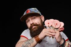 一个时兴的盖帽的愉快的有胡子的残酷人拿着一盒棒棒糖糖果 免版税图库摄影