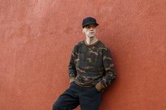 一个时兴的黑盖帽的现代帅哥在时髦牛仔裤的一件时髦的伪装衬衣在葡萄酒墙壁附近放松 库存图片