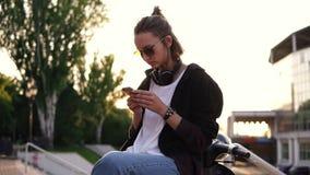 一个时兴,现代女孩坐一辆脚踏车和发短信在她的手机 她佩带牛仔裤、一件白色球衣和黑色 股票视频