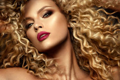 一个时装模特儿的美丽的面孔与蓝眼睛的 卷发 红色的嘴唇 免版税库存图片