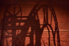 一个时钟机制的阴影与罗马数字的在砖墙上 库存照片