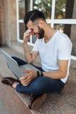 一个时髦和正面人的画象,一件白色T恤杉的,坐栏杆,与一台膝上型计算机一起使用,在前面的街道上 免版税库存照片
