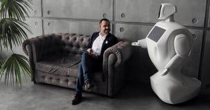 一个时髦的人与机器人沟通,按塑料机械臂到机器人,握手 控制论系统 股票视频