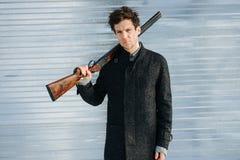一个时髦的人的冬天画象外套的有步枪的 库存图片