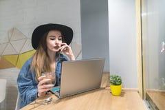 一个时髦的女孩为在一个舒适咖啡馆的一台膝上型计算机工作与一个杯子热的饮料 一个自由职业者的行家咖啡馆的画象 库存照片