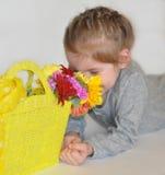 一个时髦的小女孩在有一个黄色纺织品袋子的一双灰色偶然整体和明亮的黄色运动鞋穿戴了与五颜六色的花 免版税图库摄影