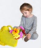 一个时髦的小女孩在有一个黄色纺织品袋子的一双灰色偶然整体和明亮的黄色运动鞋穿戴了与五颜六色的花 免版税库存照片