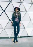 一个时髦的帽子的女孩在城市街道上 黑眼睛表面方式性感的样式妇女 免版税库存照片
