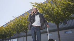 一个时髦的年轻商人的画象夹克的带着走在企业大厦附近,沟通的手提箱 股票录像