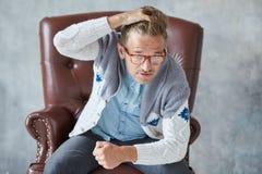一个时髦的聪明的人的画象戴眼镜的凝视入照相机,好看法,小不剃须,吸引人,蓝色衬衣, gra 免版税库存照片