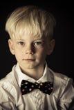 一个时髦的蝶形领结的英俊的矮小的白肤金发的男孩 免版税库存图片
