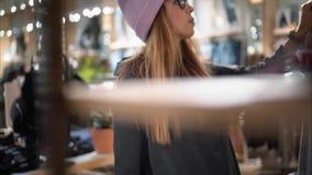 一个时髦的行家女孩走向商店机架并且选择新的玻璃 蠢材 股票录像