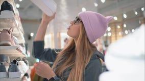 一个时髦的行家女孩走向鞋店机架并且选择新的运动鞋 股票录像