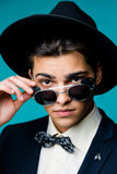一个时髦的年轻人的画象戴典雅的衣服和太阳镜的帽子的 免版税库存图片
