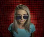 一个时髦行家女孩的画象站立在红色方格的背景的玻璃的 都市时尚的概念 库存图片