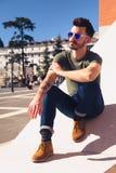 一个时髦年轻人的画象在一个晴天在城市 免版税库存图片