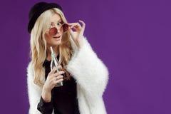 一个时兴的帽子的年轻美丽的白肤金发的妇女 从玻璃瓶的饮用的苏打 惊奇非常 库存照片