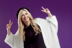一个时兴的帽子的年轻美丽的白肤金发的妇女 美好的女孩展示胜利标志 库存照片