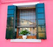 一个明亮的桃红色房子的视窗 免版税库存照片