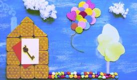 一个曲奇饼房子的Surealism概念一条木蓝天云彩背景家庭道路的 库存图片