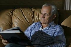 一个更老的人审查一张照片 免版税库存照片