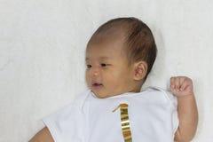 一个月大新出生的亚裔婴孩愉快地基于白色床 库存图片