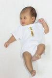 一个月大新出生的亚裔婴孩愉快地基于白色床 免版税图库摄影