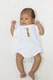 一个月大新出生的亚裔婴孩愉快地基于白色床 免版税库存照片