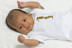 一个月大新出生的亚裔婴孩愉快地基于白色床 免版税库存图片