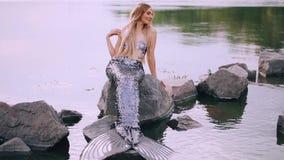一个有吸引力的美人鱼的夏天录影与长的金发和一条惊人的银色尾巴的,她践踏她的头发和轻轻地 影视素材